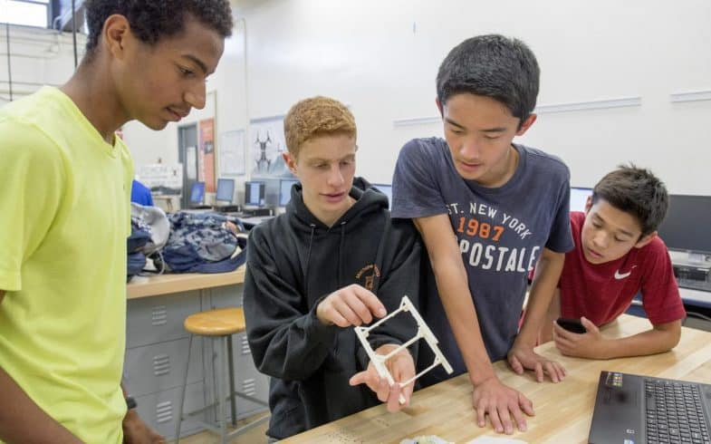 University High School students, from left, Miles Huntley-Fenner, 16, Yarin Heffes, 15, Steven Li, 15, and Kento Zollinger, 14, examine a 3-D printed frame of at miniature cube satellite they made in class. Irvine high school students are teaming up to build a miniature satellite, called a CubeSat. The project is the brainchild of two Irvine dads, who have gotten the support of two scientists from NASA/JPL who are providing advice and assistance in their free time, local tech and communications firms, and $150,000 in seed money from Irvine Public Schools Foundation.     ///ADDITIONAL INFORMATION: satellite2.0317 Ð 3/14/16 Ð LEONARD ORTIZ, ORANGE COUNTY REGISTER - _DSC5060.NEF - Students at each of Irvine's high schools are teaming up to build and launch a miniature satellite, called a CubeSat, a year from now. Once in flight, the satellite's mission is to take pictures of the moon. The project is the brainchild of two Irvine dads, who have gotten the support of two scientists from NASA/JPL who are providing advice and assistance in their free time, local tech and communications firms, and $150,000 in seed money from Irvine Public Schools Foundation. Tinh Tran is the teacher leading the students from University High.