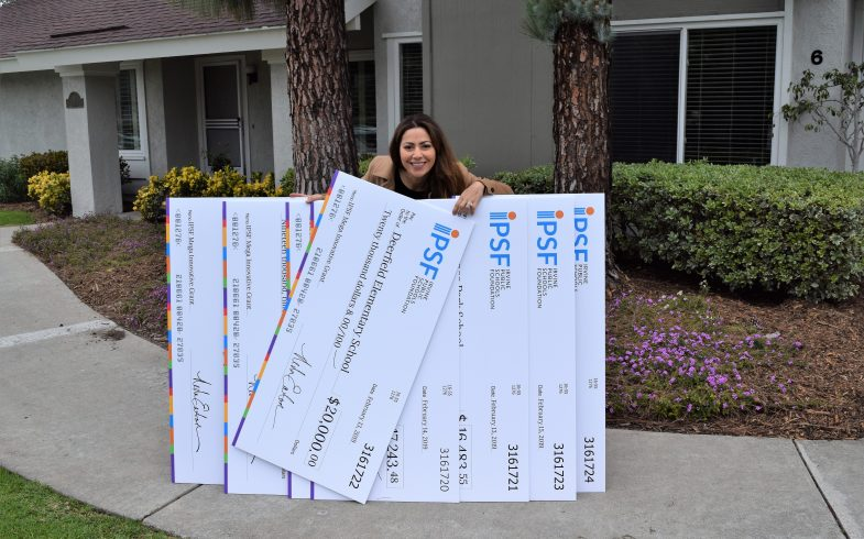 Neda Eaton with IPSF Innovative Grant Checks ready to surprise Irvine Schools with over $200K